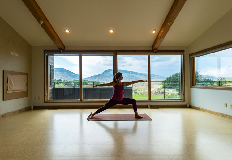 Woman doing yoga in front of window with view of mountains