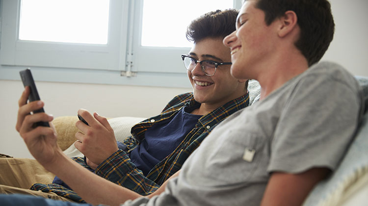 Teenage boy showing his friend the screen of his smartphone